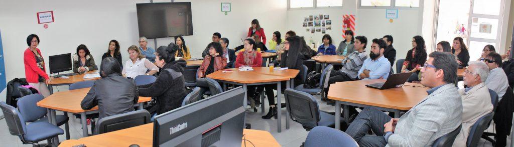 En la imagen se puede observar una sala con nueve mesas hexagonales, y al rededor de cada una de ellas se ven desde tres a cinco personas. En el salón se pueden apreciar un televisor en la pared, en dos de las mesas monitores de computador, y en una mesa se ve un computador portátil. Dos mujeres están paradas en cada borde de la pared que soporta el televisor.