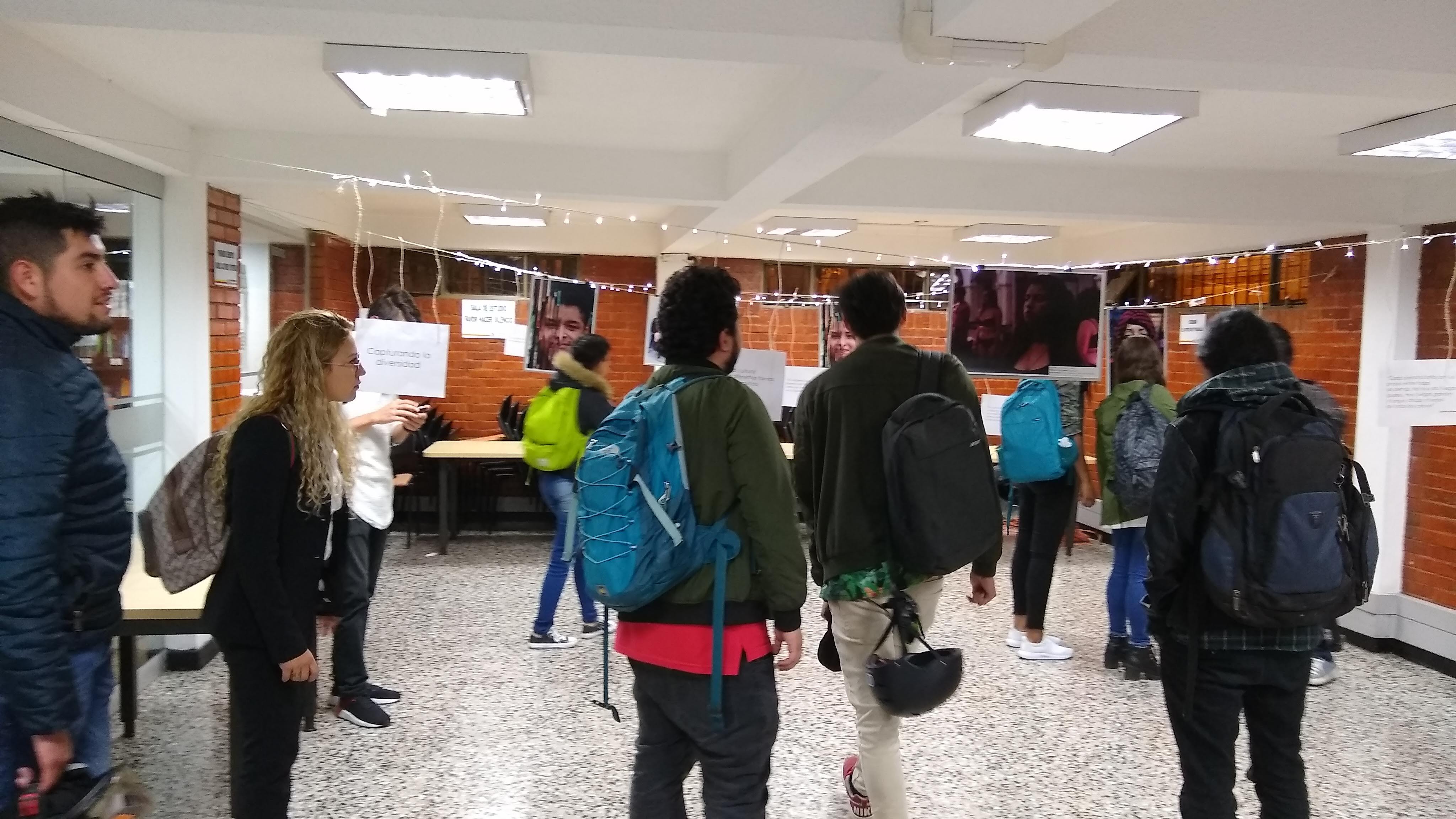 Estudiantes observando las fotografías que están colgadas en una cuerda.