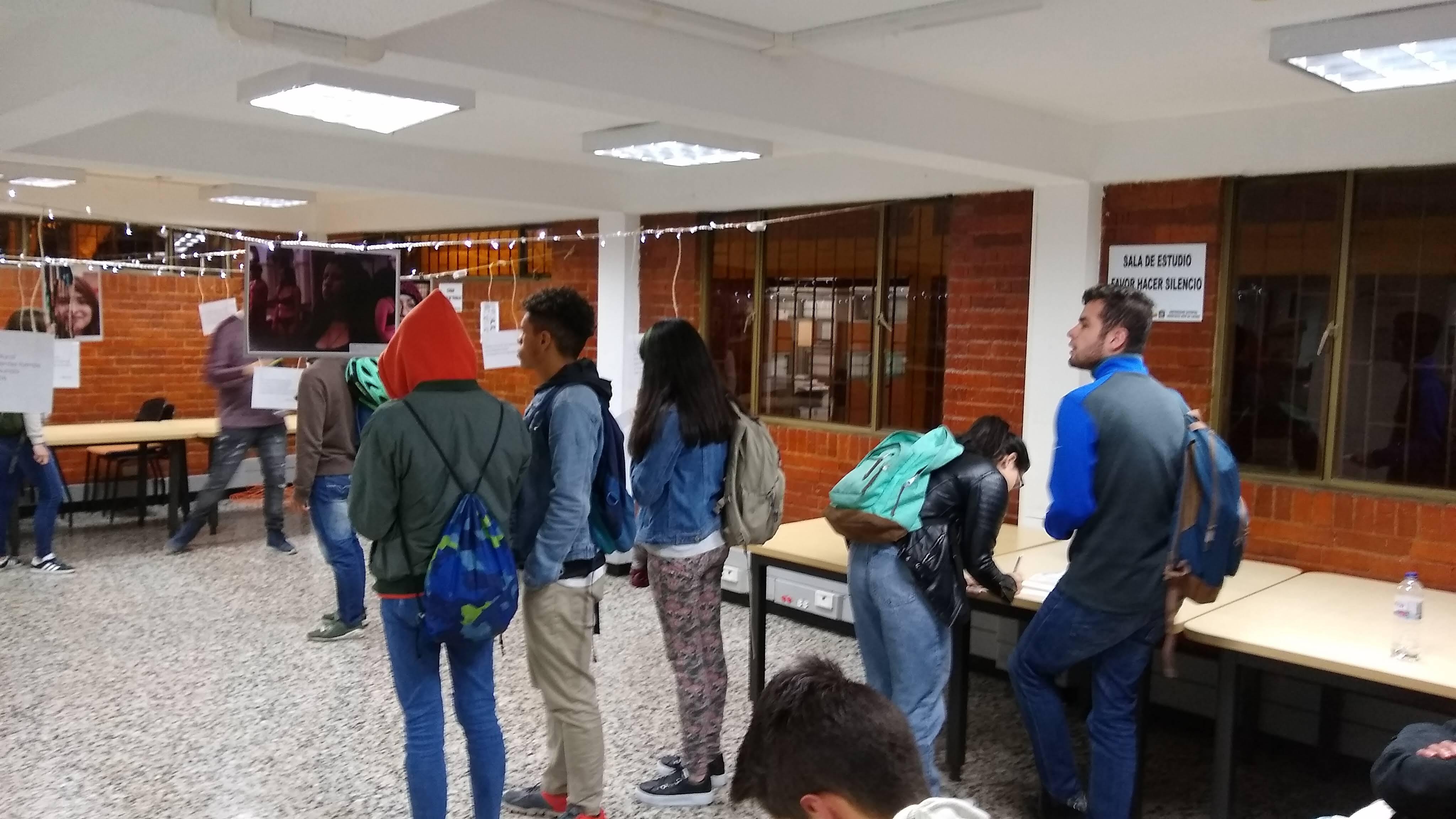 Estudiantes observando las fotografías que están colgadas y realizando la votación de la mejor foto.