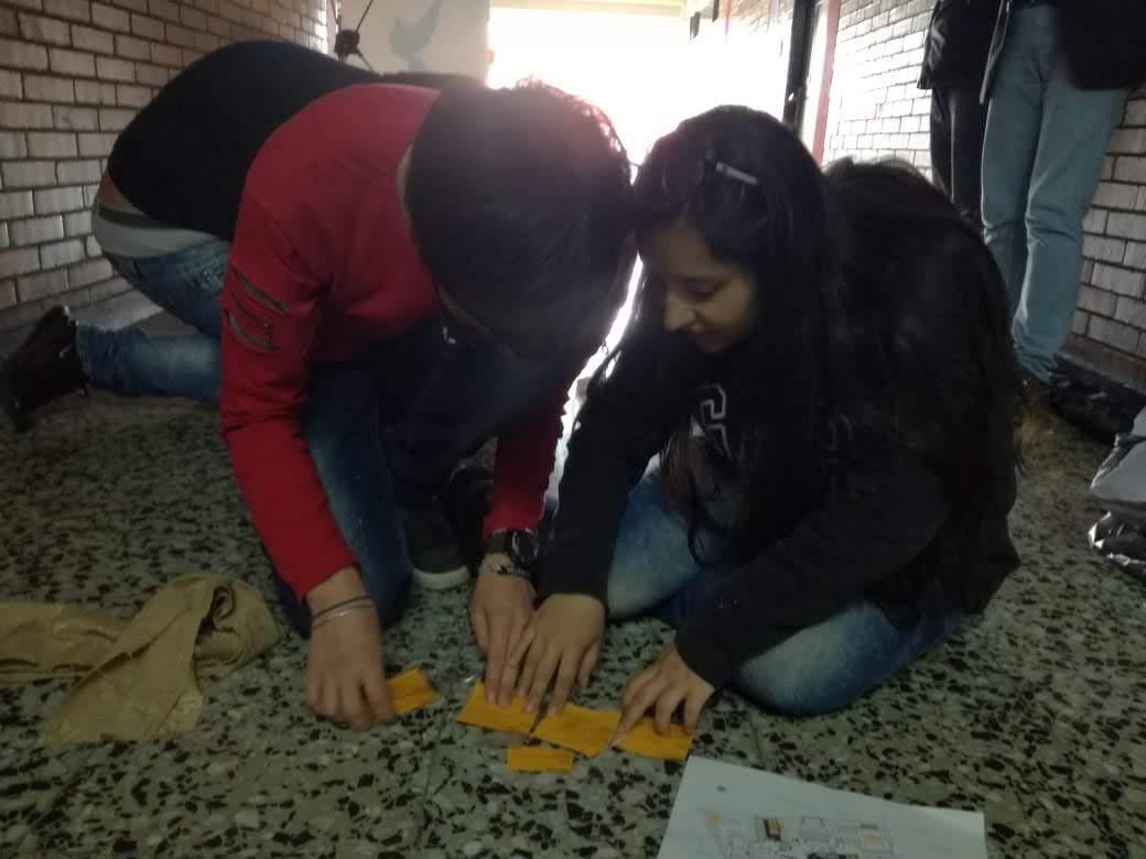 Dos estudiantes observando las tarjetas que están sobre el piso que corresponden a la actividad: En los zapatos de ...