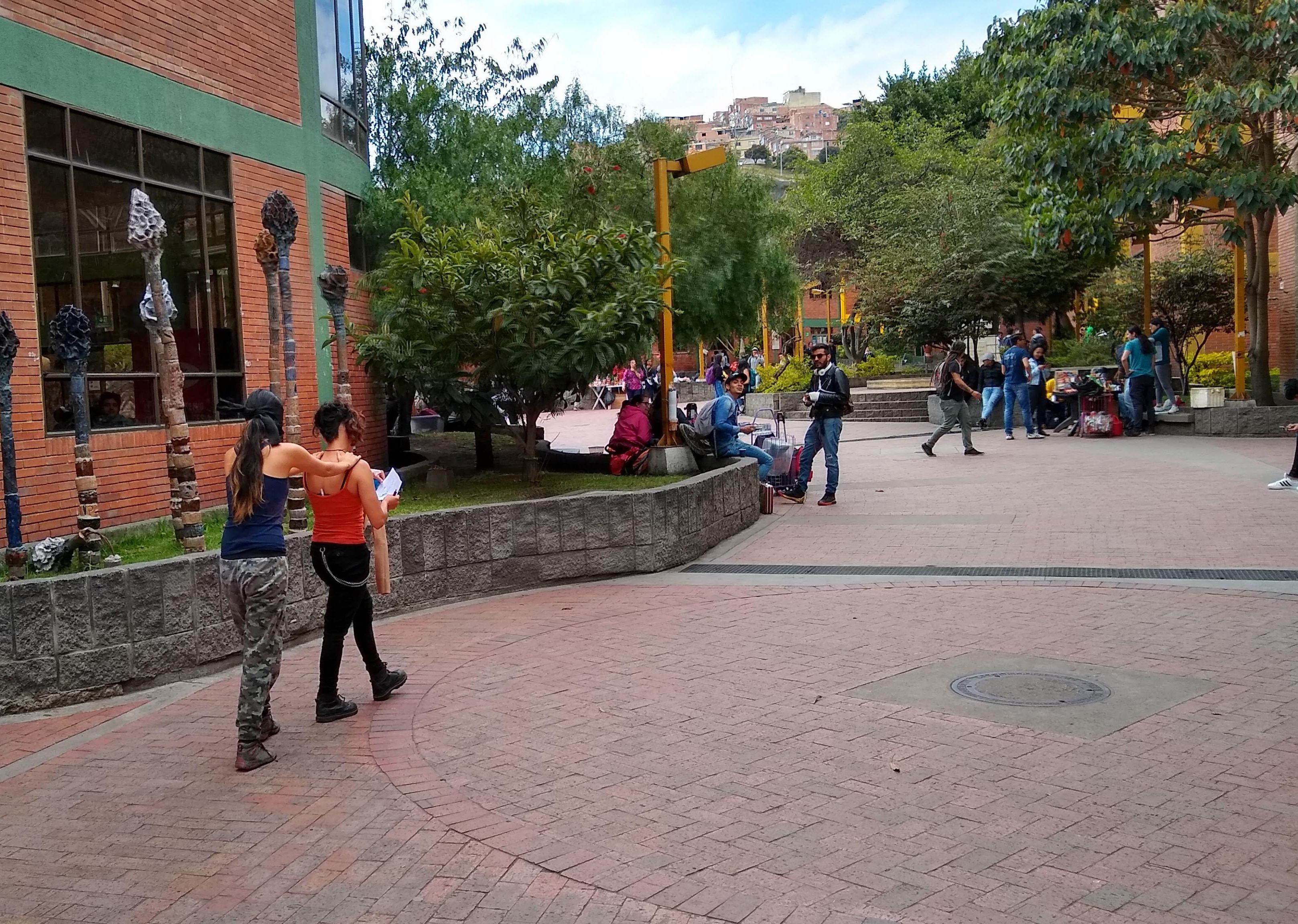 Dos estudiantes caminando en la facultad tecnológica una de ellas cogida de los hombros de la otra ya que tiene vendados los ojos