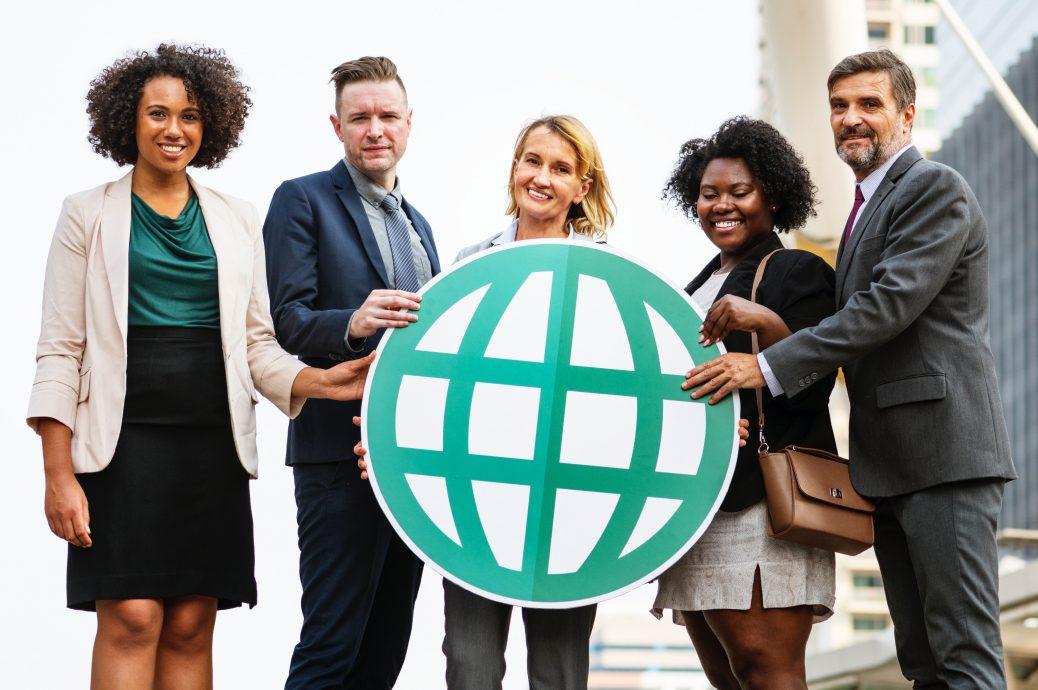 Grupo de personas tomando de la mano el icono de mundo